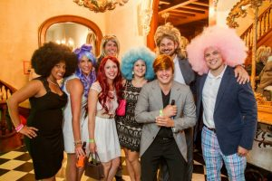 Group of attendees in big, showy wigs.