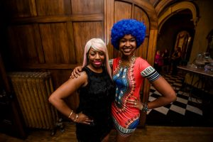Two women in large, colorful wigs at the Big Wig Ball